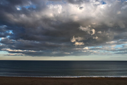 Beach in front of the sea with sky with stormy clouds in the afternoon