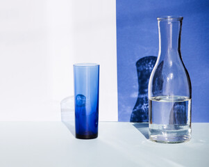 Transparent blue glass and water bottle in sunlight. Beautiful shadows fall on the background.