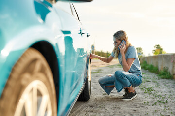 Attractive young woman looking sad, calling car service, assistance or tow truck while having...