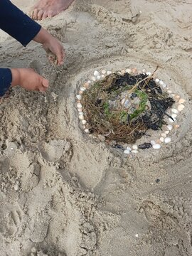 landart with kida on the beach