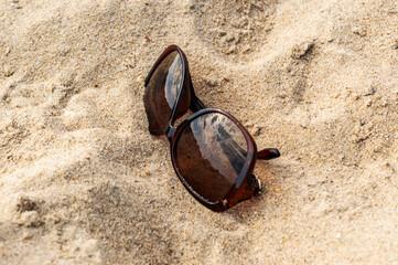 Sunglasses on the sand beach. close up.