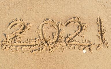 Year 2021 written on sand of sea beach.