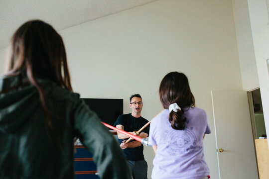 Man has a sword fight with toy sword and light saber with girls