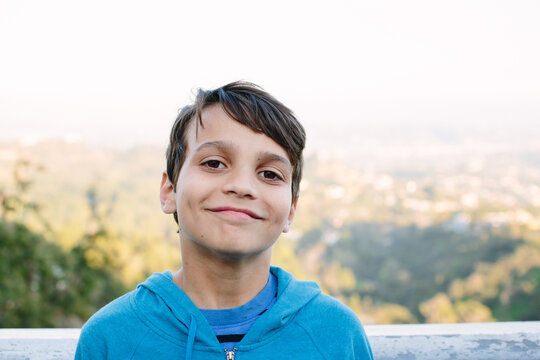 Smiling ten year old boy sands in front of a view overlook in LA