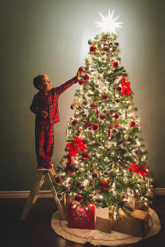 Boy hanging ornaments on Christmas Tree at night time