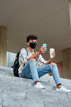 Young afro with mask uses his phone while he is sitting on the stairs