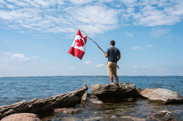Man holding Canada flag on rocky shore of a lake on a summer day.