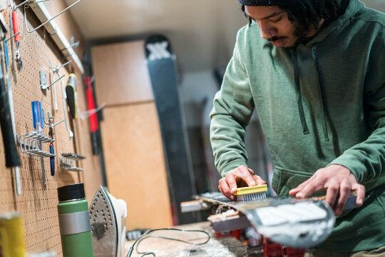 Man waxes his skis in a workshop in Lake Tahoe, CA
