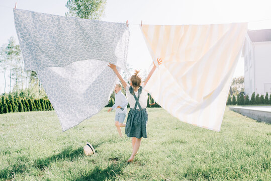 young girl dancing through the washing on the line in summer