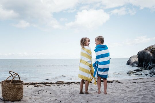 brother and sister stood laughing at the beach wrapped in towels
