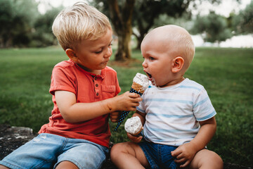 Young white toddler giving brother ice cream in a hot summer day