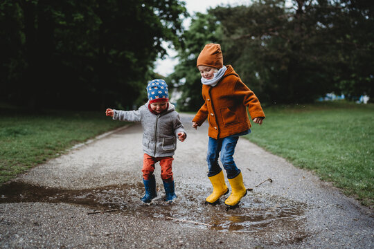 Two boys jumping in the puddles at the park on cloudy day
