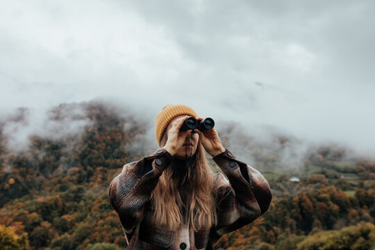 Woman walking and exploring the mountain with binoculars.