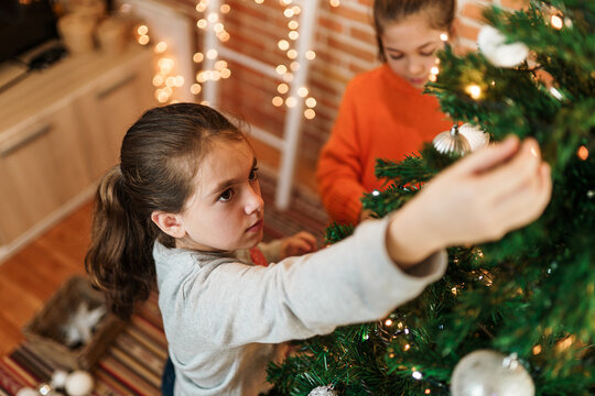Girls decorating Christmas tree at home