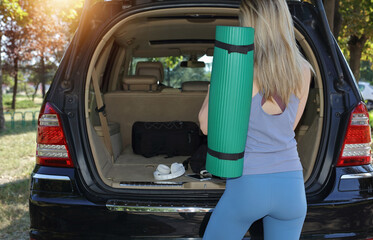 Sport woman getting ready for workout outdoor, taking exercise mat from car trunk