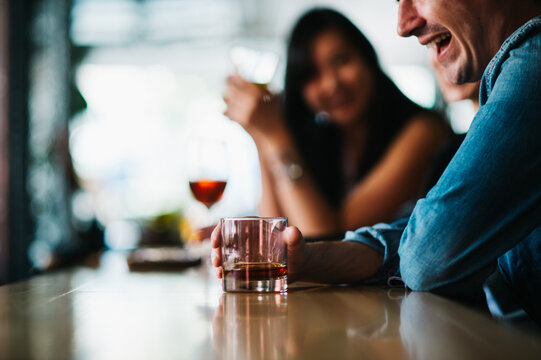 Anonymous people laughing and drinking at the bar