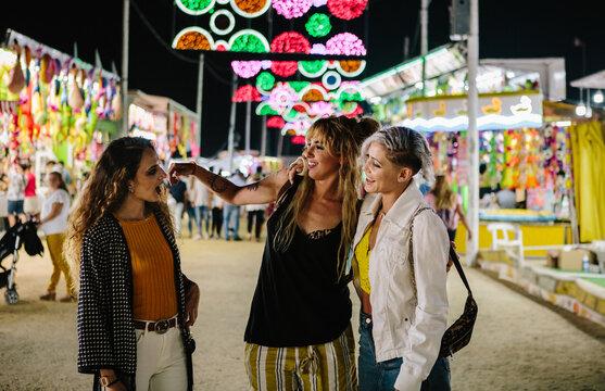 three women talking in the funfair