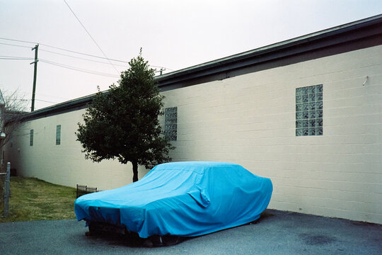 Broke down car covered with blue tarp