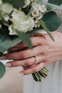 Close up of brides hands holding floral bouquet
