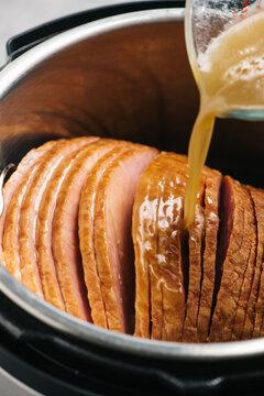 Pouring gravy over spiral ham