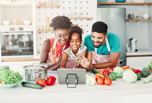family child kitchen food daughter mother father cooking preparing tablet video call waving  happy together