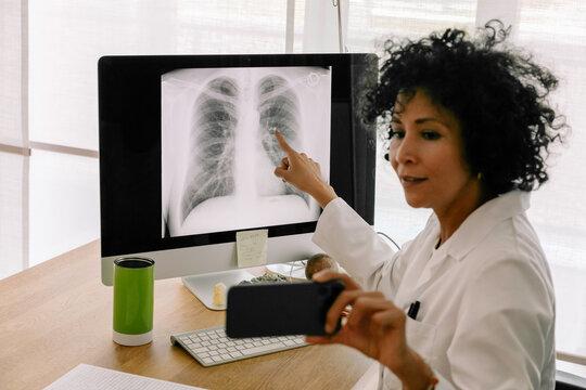 Telemedicine - Hispanic Doctor Explaining Lung X-Ray