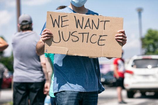 BLM: Masked Protestor Holds Sign For Justice
