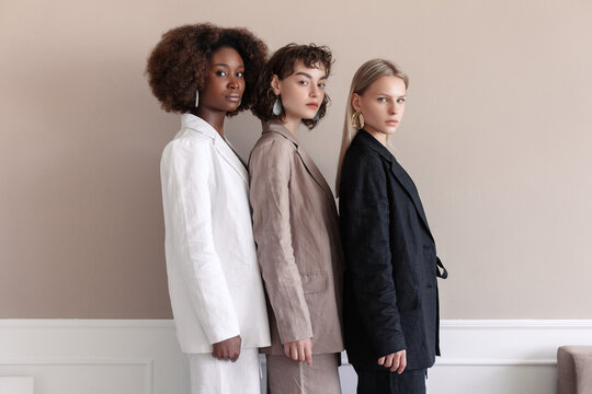 A small group of fashion multiracial multiethnic young beautiful sensual models are posing near the wall in studio room