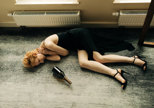Beautiful Blonde Woman lying on the floor With Bottle Of Red Win