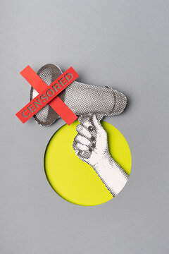 Hand holding a bullhorn censored with a red cross.