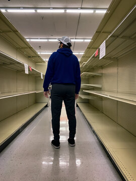 Man Looking at Empty Shelves in Store