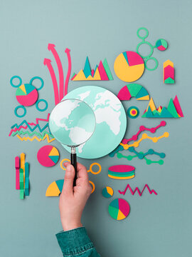 Statistics. Hand with a magnifying glass looking in a world map focusing in America.