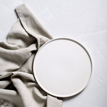 White background round plate, fork, knife and napkin