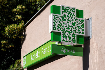 Stettin, Poland,2020: Sign with green-white pattered logo of a polish pharmacy mounted on a wall.