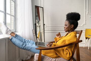 Happy African American woman freelancer with afro hairstyle wear yellow cardigan resting, sitting...
