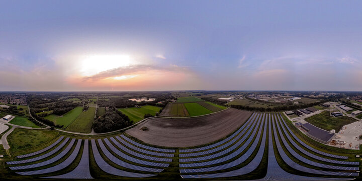 Aerial view of solar panel station with long rows of power supply in farmland surroundings at sunset. 360 degree aerial panorama ready for use in 3D environment mapping and 360VR.