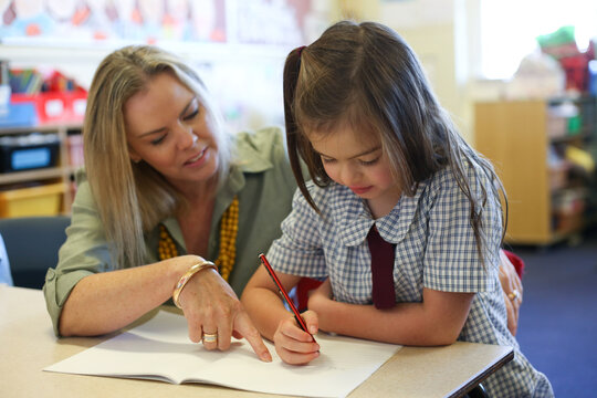 Female school teacher helping student with her work