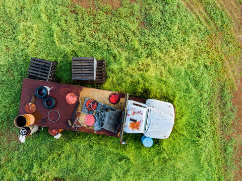 Truck and old farm junk seen from overhead on green farm