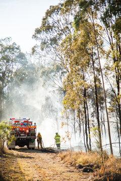 NSW rural fire service volunteer firefighter beside truck in fire smoke