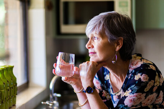 Portrait of a healthy senior woman leaning on the kitchen bench drinking a glass of water