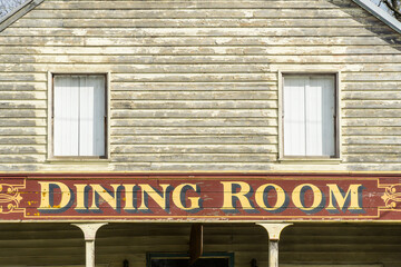 A close up of an old style painted sign on the side of a weathered building
