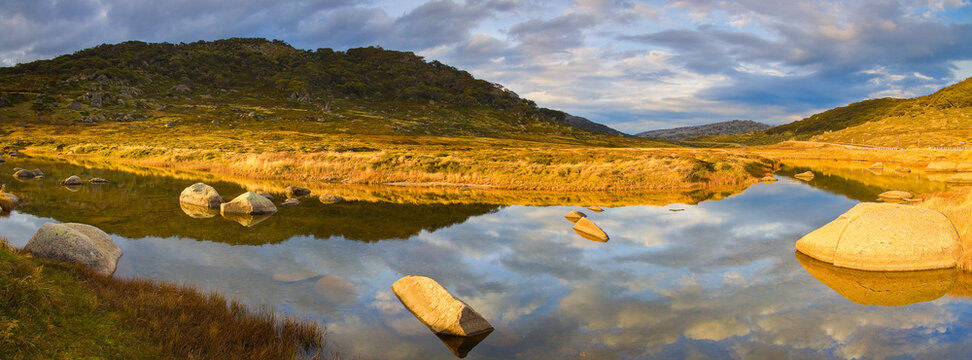 Reflections of a dramatic sky over a mountain stream