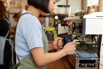 Young female barista preparing coffee with coffee machine in shop