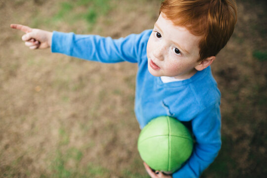 Looking down at a young boy holding a football and pointing