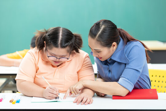 portrait asian disabled child or autism child writing a book and woman teacher helping in classroom