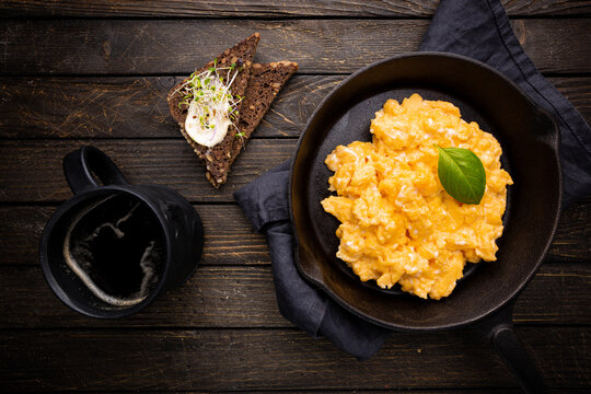 Fresh cooked scrambled eggs in a cast iron skillet on dark wooden background, top view