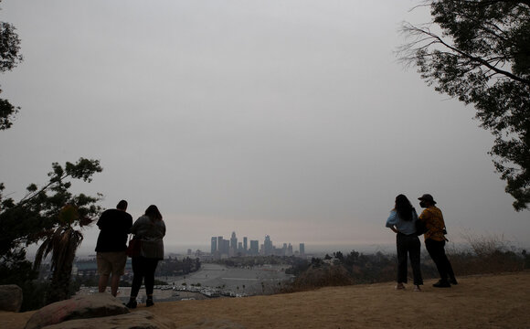 Couples watch downtown from Angels Point at sunset in a smoke haze generated by the Bobcat fire in Los Angeles