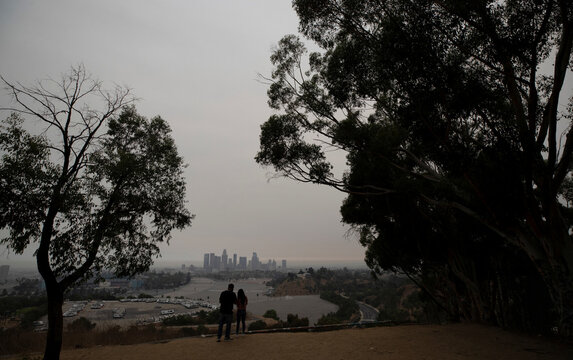 A couple watches downtown from Angels Point at sunset in a smoke haze generated by the Bobcat fire in Los Angeles