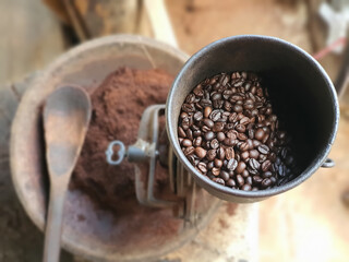 Coffee beans are in a coffee grinder with ground coffee as blurred background. Farm Agricultural products from hill tribe.