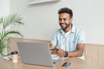 Young handsome man using laptop at home, Businessman or student working online on computer indoors,...